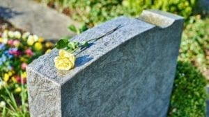 withered yellow rose on gravestone